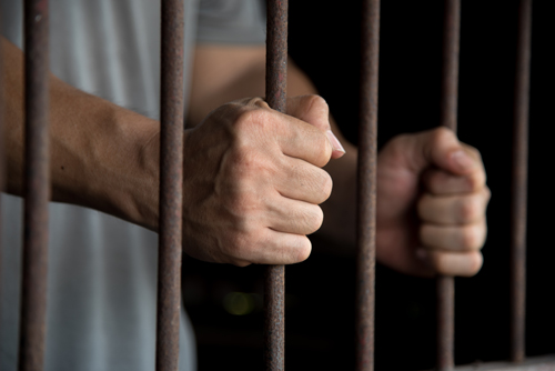 addiction treatment vs. prison - hands jail cell bars - willingway