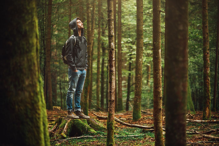 Why Being in Nature Is Good for You - young man in forest with hoodie and backpack