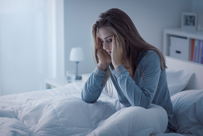 Handling-Insomnia-While-in-Recovery - tired woman in bed upset