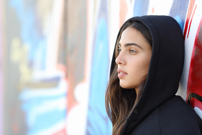 Signs-Your-Teen-Has-a-Substance-Abuse-Problem - pretty young lady in hoodie grafitti wall background