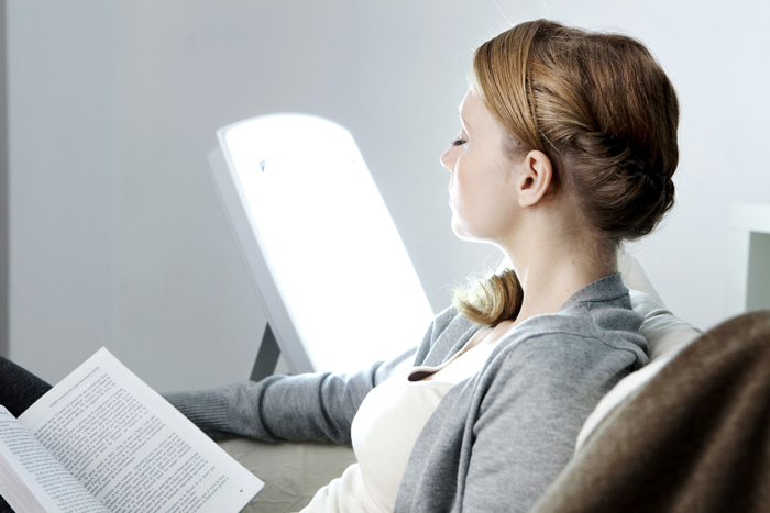 Understanding-How-SAD-May-Affect-Your-Mood - woman using light therapy lamp