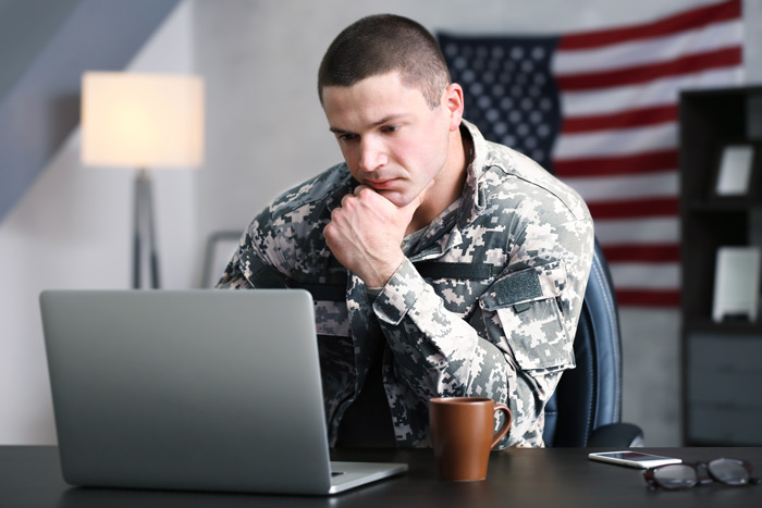 military man in office looking at laptop