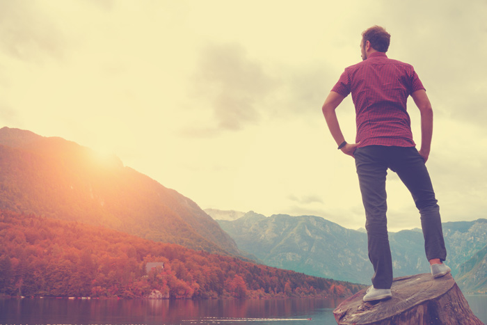 triumphant man standing looking out at mountains during sunset - quotes and affirmations