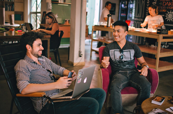 two young men talking in lively coffee shop - sponsor