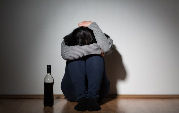 sad woman hugging knees to chest near bottle of liquor - women are