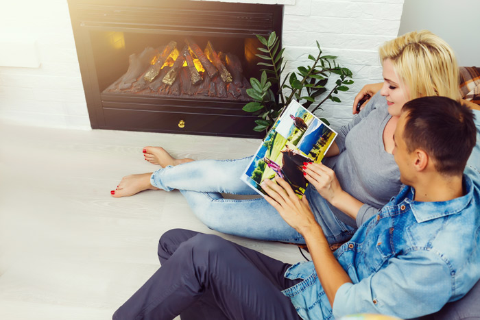 young couple sitting on floor of home looking at photo album together - Valentine's