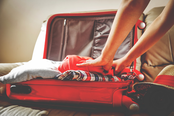 closeup - person packing a suitcase - short-term