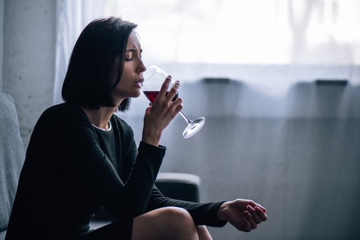woman drinking glass of red wine at home - your drinking