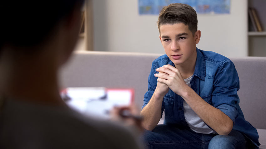 teenage boy talking to his therapist - young adult drug rehab center - teen drug rehab