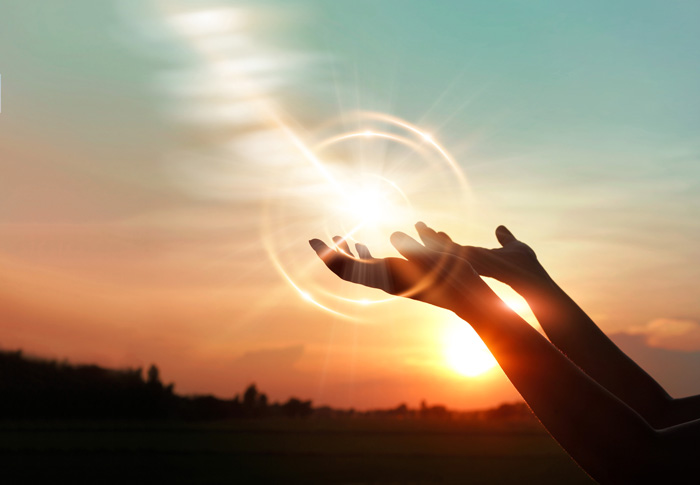 closeup of person's hands being held up to the sky during sunrise - spirituality in recovery