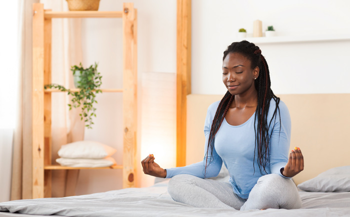 beautiful African American woman sitting on bed meditating - rituals and routines