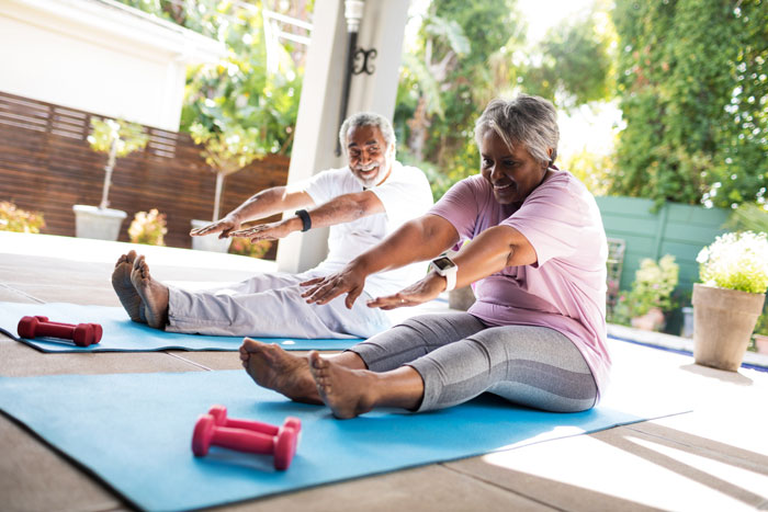 senior Black couple doing stretching exercises on mats together - exercise