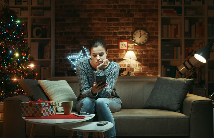 young woman sitting at home during the holidays looking lonely, looking down at smart phone while on couch at home