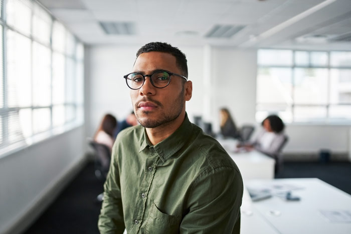 handsome serious looking young Black man at work in office - high-functioning
