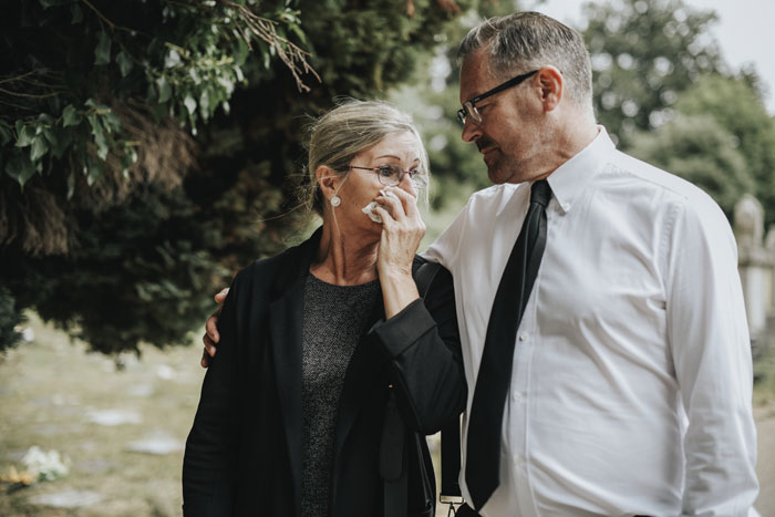 middle aged man and woman walking outdoors after funeral or burial - drug overdoses