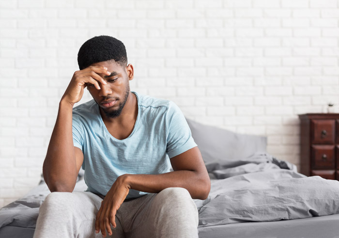 handsome young Black man sitting on the edge of his bed looking distraught - clonazepam withdrawal