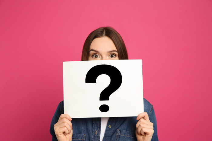 woman holding white sign with black question mark on it against pink background - willpower