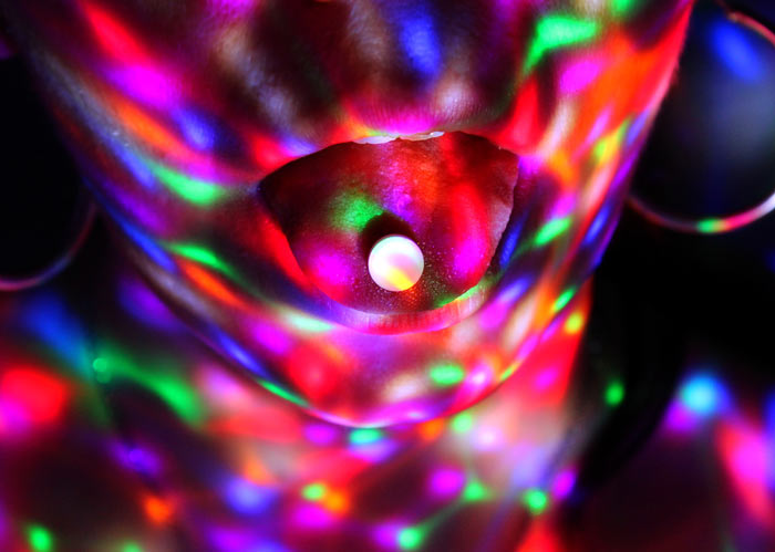 closeup of pill on person's tongue; brightly colored lights reflect on their face - club drugs