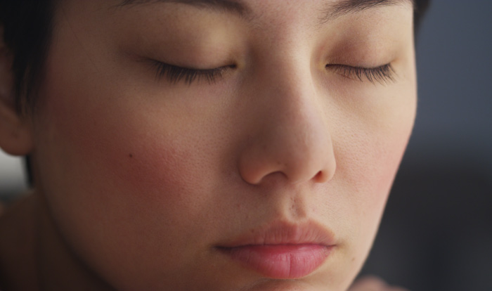 closeup of Asian woman with her eyes closed - mindfulness