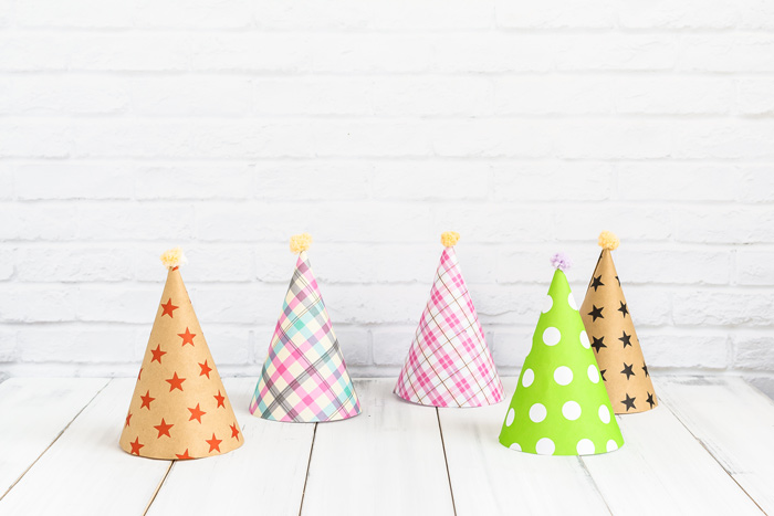 colorful paper party hats sitting on white wooden table - fun
