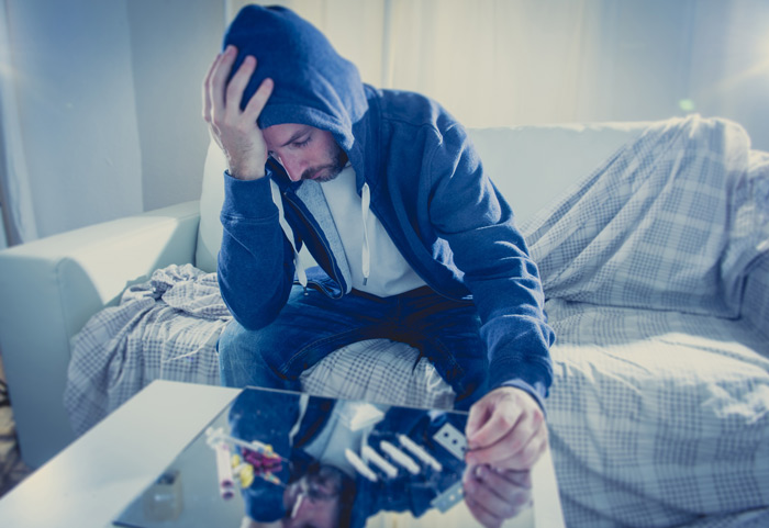 sad man in a hoodie cutting lines of cocaine on a table at home - cocaine addiction